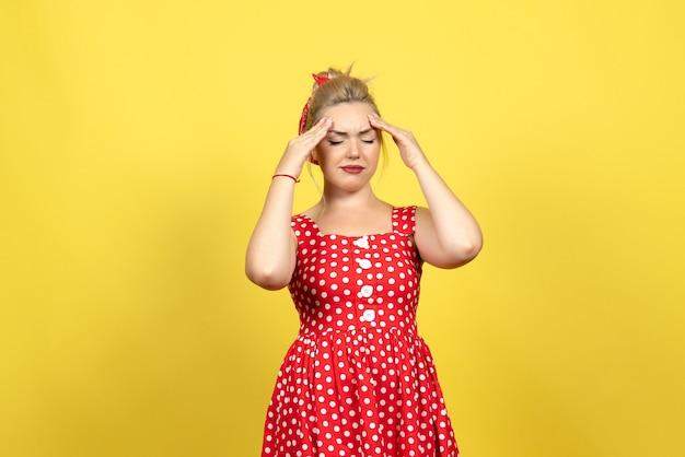 Jonge vrouw in rode polka dot jurk die lijden aan hoofdpijn op geel