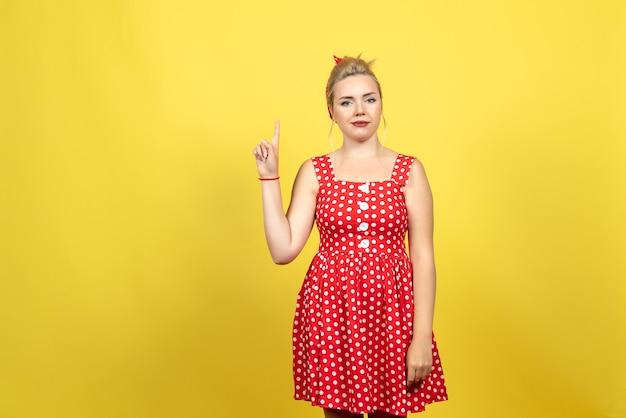 Jonge vrouw in rode polka dot jurk haar vinger op geel