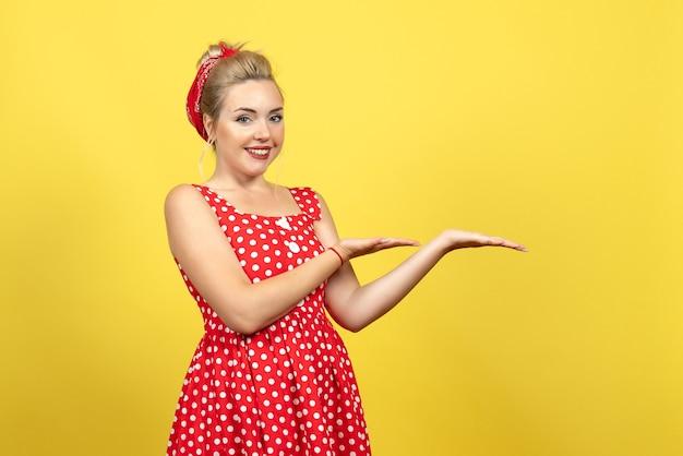 Jonge vrouw in rode polka dot jurk lachend op geel