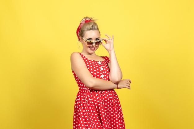 Jonge vrouw in rode polka dot jurk met zonnebril poseren op geel