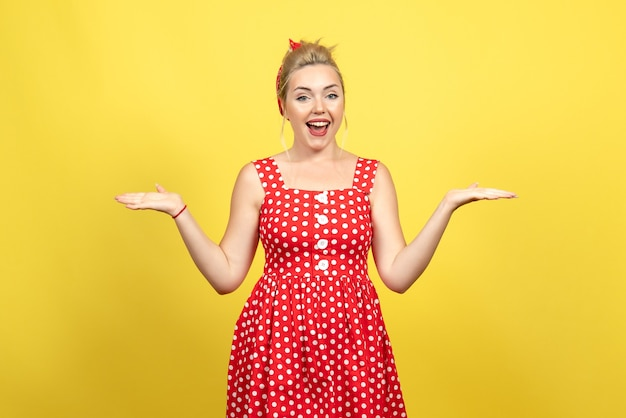 Jonge vrouw in rode polka dot jurk poseren op geel