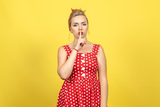 Jonge vrouw in rode polka dot jurk vragen stil te zijn op geel