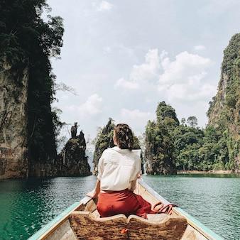 Jonge vrouw in rode rok en witte blouse zittend op houten boot kijken op exotische en tropische donkergroene grote eilanden met rotsen en turquoise meer in thailand reizen vakantie en avontuur concept