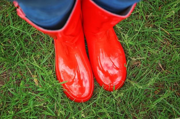 Jonge vrouw in rode rubberen laarzen op groen gras