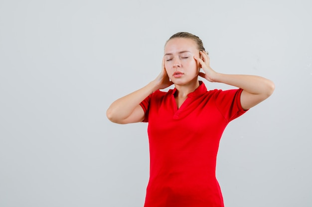 Jonge vrouw in rode t-shirt hand in hand en kijkt moe