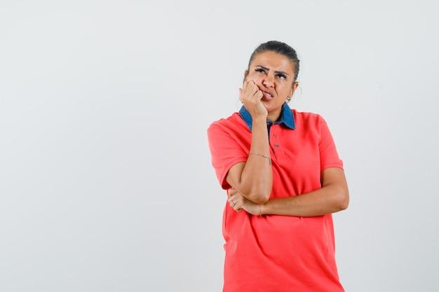 Jonge vrouw in rode t-shirt leunende hand op de wang, staande in denken pose en peinzend op zoek, vooraanzicht.