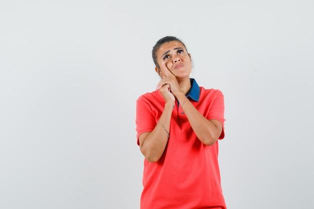 Jonge vrouw in rode t-shirt leunende wang aan kant en peinzend, vooraanzicht kijkt.