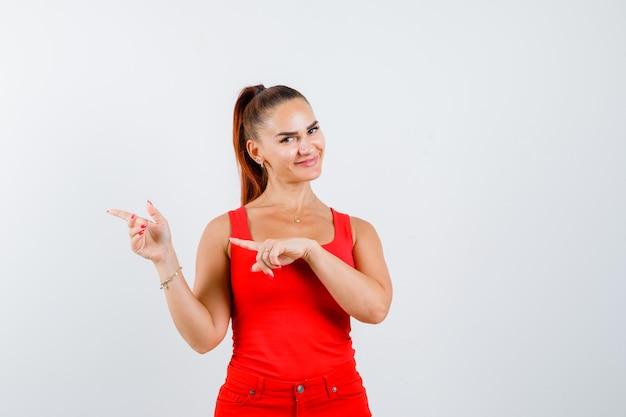 Jonge vrouw in rode tanktop, broek wijst naar de zijkant en kijkt voorzichtig, vooraanzicht.