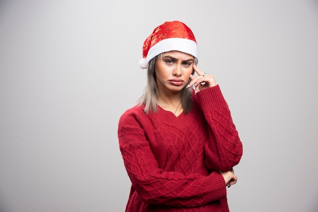 Jonge vrouw in rode trui die intens denkt.