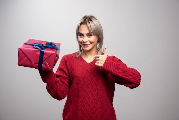 Jonge vrouw in rode trui die kerstcadeau vasthoudt en duimen opgeeft.