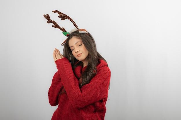 Jonge vrouw in rode trui en herten hoofdband op witte muur.