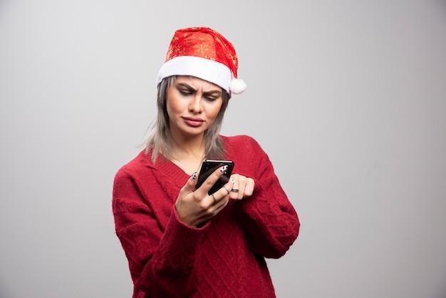 Jonge vrouw in rode trui kijken intens naar mobiele telefoon op grijze achtergrond.