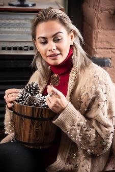 Jonge vrouw in rode trui met een houten mand vol dennenappels