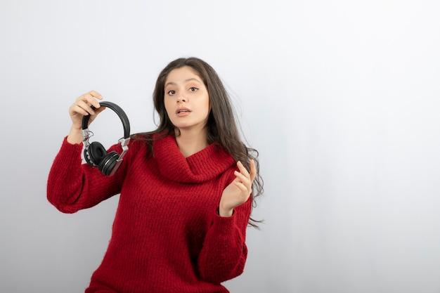 Jonge vrouw in rode trui opstijgen koptelefoon.