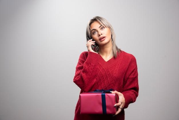 Jonge vrouw in rode trui praten op mobiele telefoon.