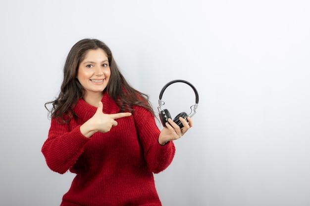 Jonge vrouw in rode trui wijzend op koptelefoon.
