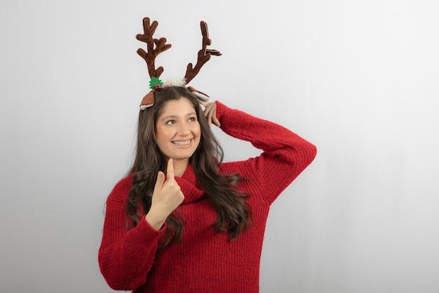 Jonge vrouw in rode warme trui en herten hoofdband op witte muur.