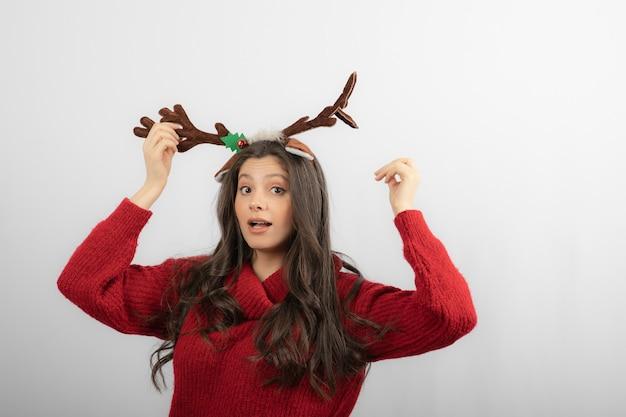 Jonge vrouw in rode warme trui en herten hoofdband.