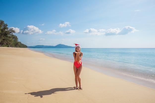 Jonge vrouw in rode zwempak en kerstmanhoed die luchtkus verzenden