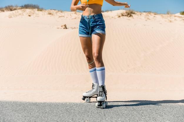 Jonge vrouw in rollen op kant van de weg
