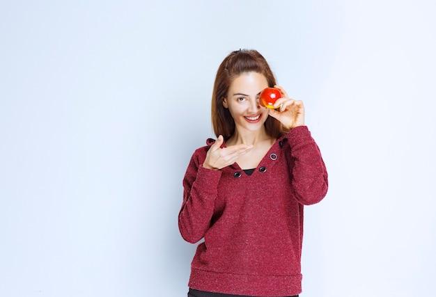 Jonge vrouw in rood jasje die een rode appel aan haar oog houdt