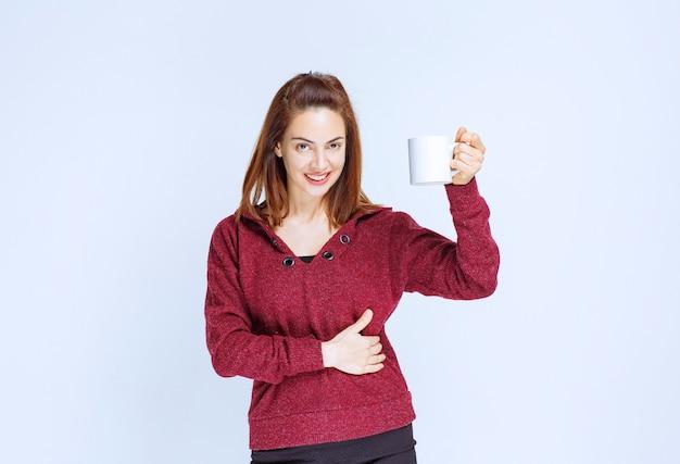 Jonge vrouw in rood jasje die een witte koffiemok houdt en positief handteken toont