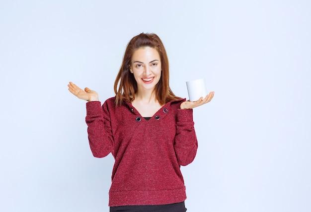 Jonge vrouw in rood jasje die een witte koffiemok houdt