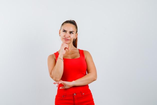 Jonge vrouw in rood mouwloos onderhemd, broek die hand op kin houdt en verbaasd, vooraanzicht kijkt.
