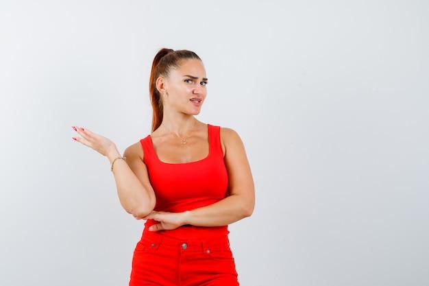 Jonge vrouw in rood mouwloos onderhemd, broek die handpalm uitspreidt en onrustig, vooraanzicht kijkt.