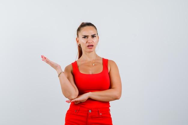 Jonge vrouw in rood mouwloos onderhemd, broek die handpalm uitspreidt en wrokkig, vooraanzicht kijkt.