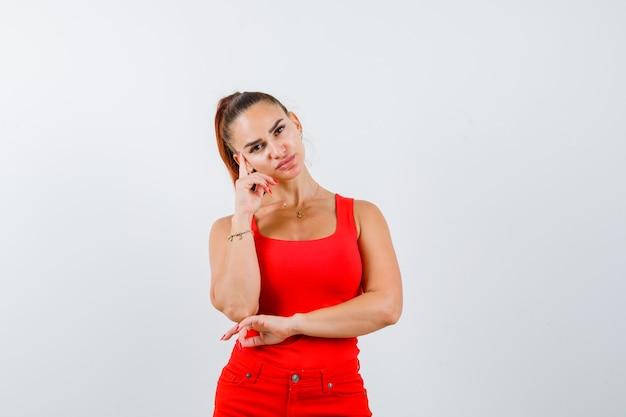 Jonge vrouw in rood mouwloos onderhemd, broek die het hoofd op vingers leunt en weemoedig kijkt, vooraanzicht.