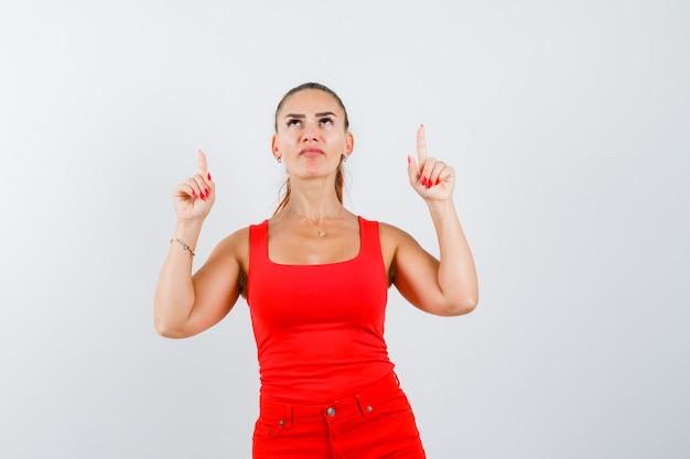 Jonge vrouw in rood mouwloos onderhemd, broek die omhoog wijst en weemoedig kijkt, vooraanzicht.