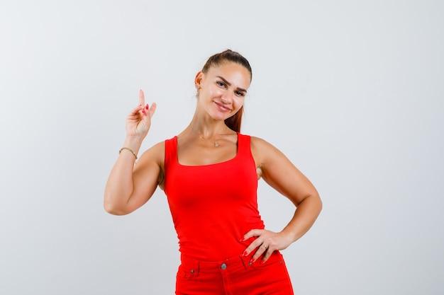 Jonge vrouw in rood mouwloos onderhemd, broek die v-teken toont en vredig, vooraanzicht kijkt.
