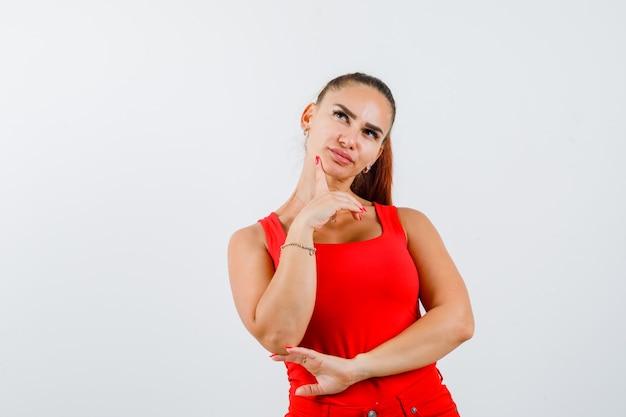 Jonge vrouw in rood mouwloos onderhemd, broek die zich in het denken stelt stelt en peinzend kijkt, vooraanzicht.