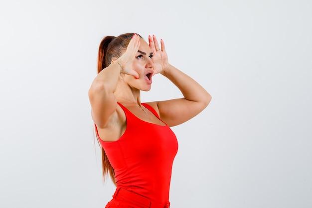 Jonge vrouw in rood mouwloos onderhemd, broek hand in hand aan de zijkanten van het gezicht en op zoek verbaasd, vooraanzicht.