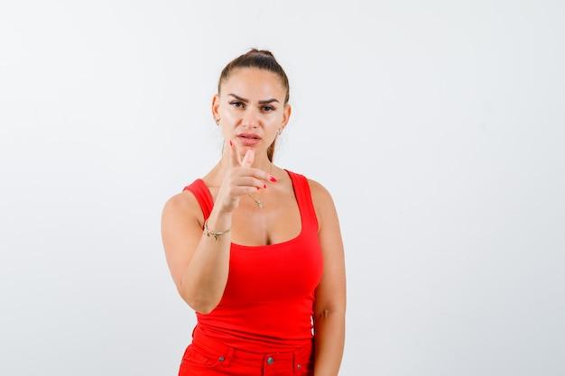 Jonge vrouw in rood mouwloos onderhemd, broek wijzend op camera en op zoek zelfverzekerd, vooraanzicht.