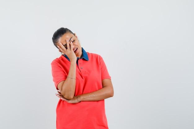 Jonge vrouw in rood overhemd dat een deel van het gezicht bedekt met hand en vermoeid, vooraanzicht kijkt.