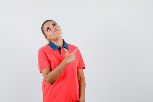 Jonge vrouw in rood overhemd die rechtsboven met wijsvinger richt en hierboven kijkt en mooi, vooraanzicht kijkt.