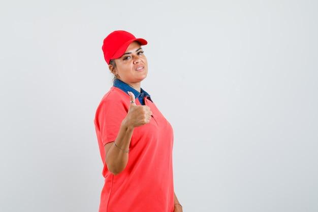 Jonge vrouw in rood overhemd en glb die duim tonen en mooi, vooraanzicht kijken.