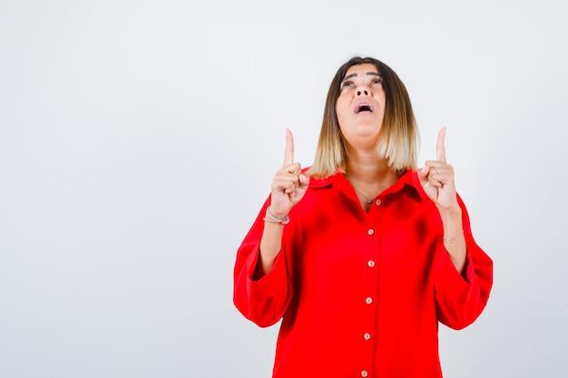 Jonge vrouw in rood oversized shirt die omhoog wijst en verbaasd kijkt, vooraanzicht.