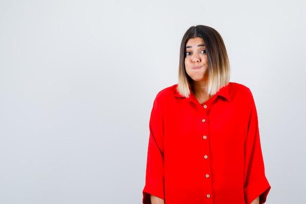 Jonge vrouw in rood oversized shirt die op de wangen blaast en er grappig uitziet, vooraanzicht.