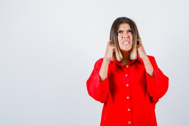 Jonge vrouw in rood oversized shirt die oren met vingers inplugt en er geïrriteerd uitziet, vooraanzicht.