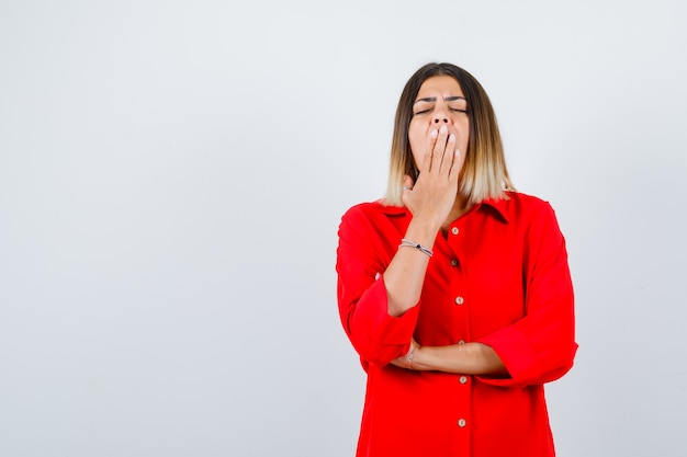 Jonge vrouw in rood oversized shirt geeuwen en slaperig kijken, vooraanzicht.
