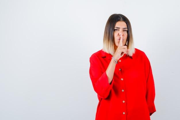 Jonge vrouw in rood oversized shirt met stiltegebaar en zelfverzekerd, vooraanzicht.