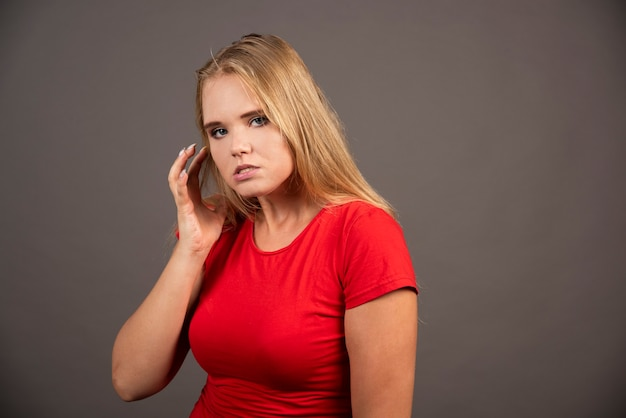 Jonge vrouw in rood shirt poseren op zwarte muur.