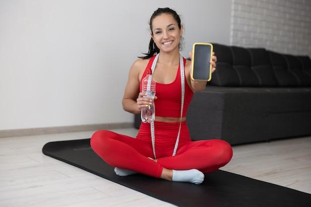 Jonge vrouw in rood trainingspak die thuis oefening of yoga doet. vrolijk positief meisje toont smartphone-scherm en glimlach. waterfles in de hand houden en meetlint om de nek.