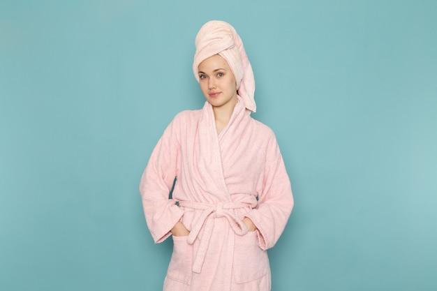 Jonge vrouw in roze badjas na douche gewoon poseren op blauw