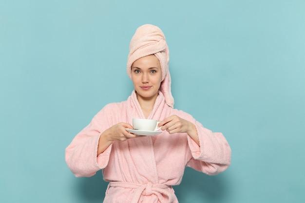 Jonge vrouw in roze badjas na douche koffie drinken met een glimlach op blauw
