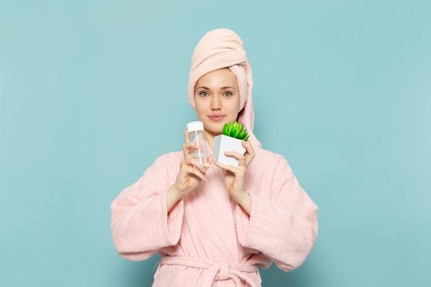 Jonge vrouw in roze badjas na douche met plantje en spray op blauw
