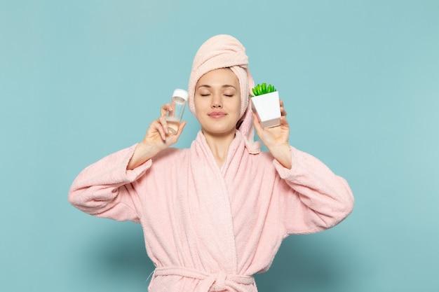 Jonge vrouw in roze badjas na douche met spray en groene plant op blauw